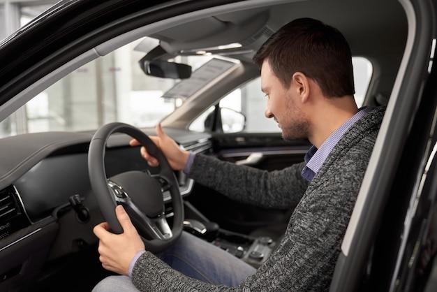 Klient siedzący w fotelu kierowcy kabiny samochodowej.