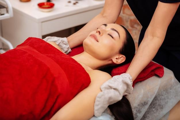 Klient szorujący. spokojna, ładna pani śpiąca, podczas gdy mistrz pielęgnuje jej skórę specjalnymi rękawiczkami