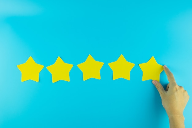 Klient trzyma pięć gwiazdową koloru żółtego papieru notatkę na błękitnym tle. recenzje klientów, opinie, oceny, ranking i koncepcja usług.