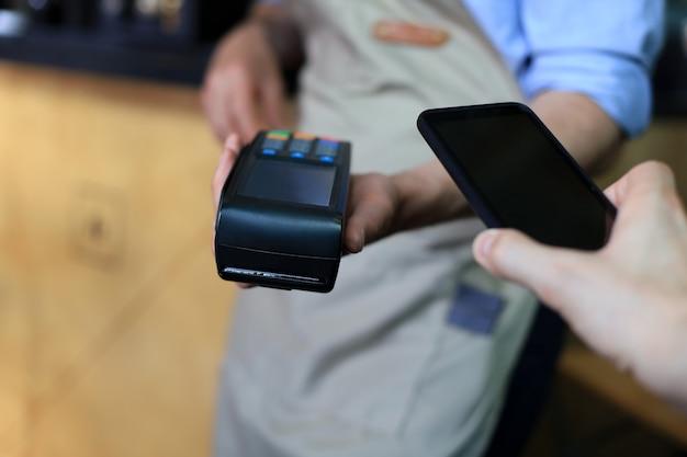 Klient używający smartfona do płatności na rzecz właściciela w kawiarni restauracji, technologia bezgotówkowa.