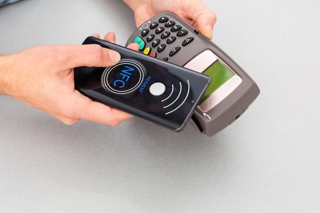 Klient używający telefonu komórkowego do płatności przez nfc