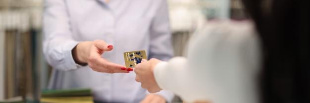 Klient wręczający sprzedawcom kartę kredytową z bliska rejestracja zamówień w szyciu