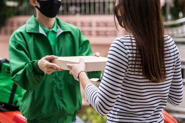 Klient z maską przyjmuje pizzę z dostawą