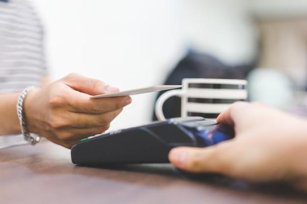Klient za pomocą karty kredytowej do płacenia rachunku za pomocą koncepcji płatności zbliżeniowych