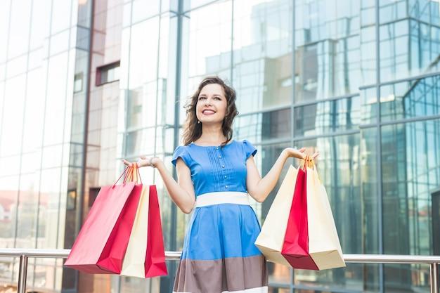 Klient. zakupoholiczka zakupy kobieta trzyma wiele toreb na zakupy podekscytowany. koncepcja uzależnienia