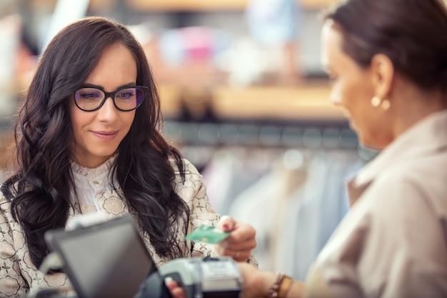 Klientka korzystająca z płatności kartą zbliżeniową za ubrania w sklepie.