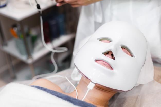 Klientka leży w salonie na stole kosmetycznym z białą maską na twarzy
