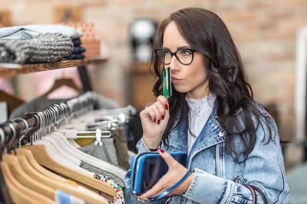 Klientka myśli o swoich możliwościach zakupów w sklepie z modą, trzymając w ręku kartę płatniczą.