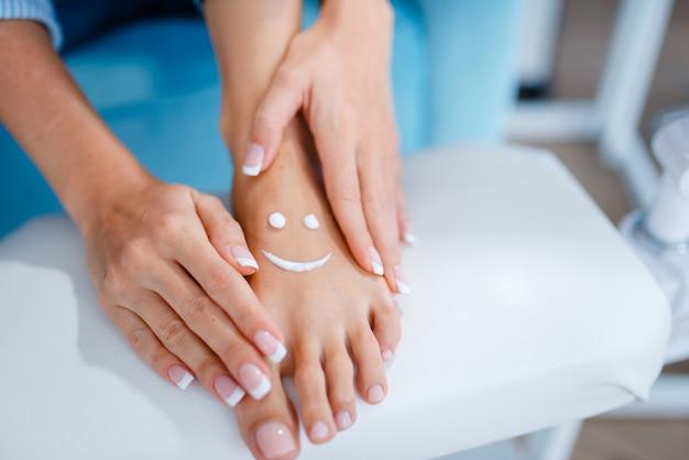 Klientka pokazuje perfekcyjnie wykonane paznokcie w salonie kosmetycznym.