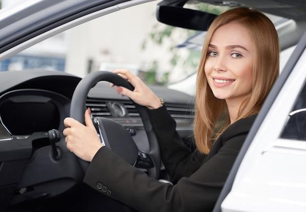 Klientka salonu samochodowego siedzi w białym samochodzie