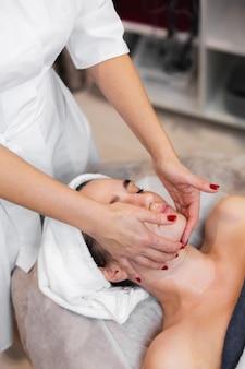 Klientka w salonie otrzymująca ręczny masaż twarzy od kosmetyczki
