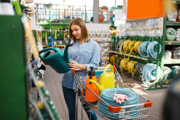 Klientka wybierająca narzędzia ogrodnicze w sklepie dla ogrodników. kobieta kupująca sprzęt w sklepie do kwiaciarstwa, zakup instrumentów kwiaciarskich