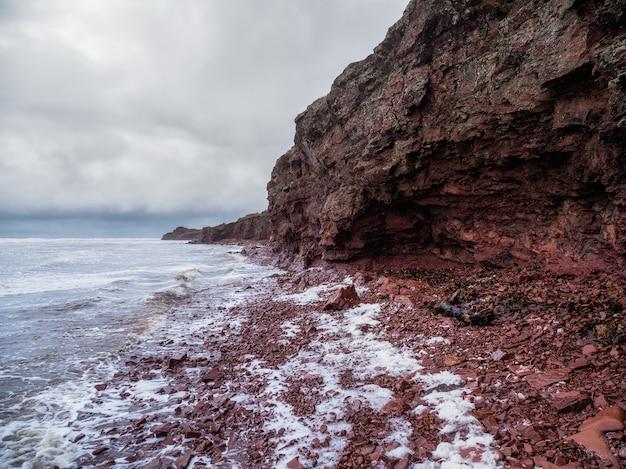Klif nad morzem z wąską linią brzegową. fale z białą pianką toczą się po skalistym brzegu. tersky coast, cape ship na półwysep kolski.