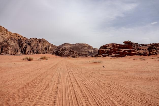 Klify i jaskinie na pustyni pełnej suchej trawy pod zachmurzonym niebem w ciągu dnia