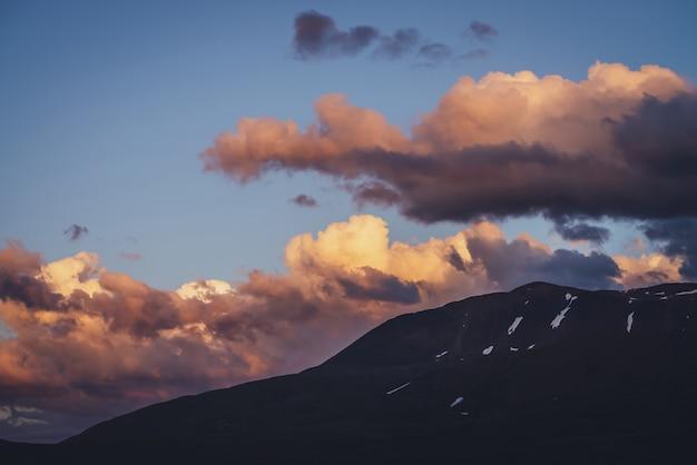 Klimatyczna sceneria górska z liliowym niebem świtu. malowniczy krajobraz z rozświetlonym zachodem słońca w górach. piękny wschód słońca w górach w pastelowych kolorach. rozświetlający kolor w pochmurnym niebie o świcie.