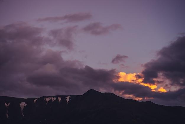 Klimatyczna sceneria górska z liliowym niebem świtu. malowniczy krajobraz ze skałami ze śniegiem pod fioletowym niebem słońca. piękny wschód słońca w górach w pastelowych kolorach. rozświetlający kolor w pochmurnym niebie o świcie.