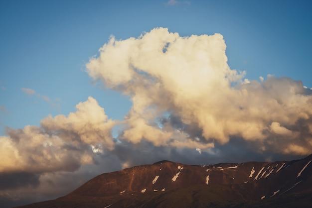 Klimatyczna sceneria górska z żółtymi chmurami w błękitne niebo. malowniczy krajobraz z rozświetlonymi chmurami zachód słońca nad górami ze śniegiem. piękny wschód słońca w górach. śnieg na skałach w słońcu.