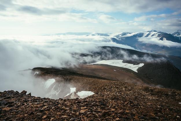 Klimatyczna sceneria na szczycie grzbietu górskiego nad gęstymi, niskimi chmurami. malowniczy widok od krawędzi przepaści nad chmurami do zaśnieżonych gór. piękny alpejski krajobraz z pasmem górskim nad gęstymi chmurami.