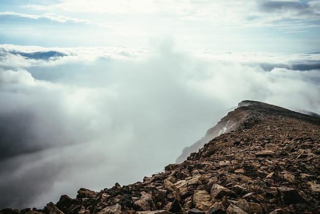 Klimatyczna sceneria wyżyn na szczycie grzbietu górskiego nad gęstymi, niskimi chmurami. minimalistyczny widok z krawędzi przepaści nad chmurami. piękny minimalistyczny alpejski krajobraz z pasmem górskim nad gęstymi chmurami