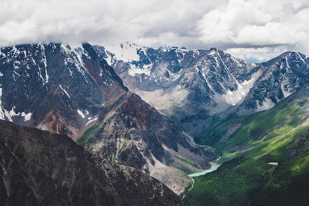 Klimatyczny alpejski krajobraz z masywnym wiszącym lodowcem na gigantycznych skałach i dolinie z górskimi jeziorami. duży język lodowca. niskie chmury nad ośnieżonymi górami. majestatyczne krajobrazy na dużej wysokości.