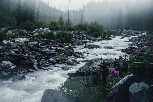 Klimatyczny deszczowy krajobraz z różowymi kwiatami na tle potężnej górskiej rzeki w ulewnym deszczu