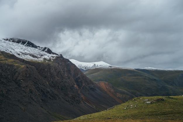 Klimatyczny krajobraz alpejski z głębokim wąwozem i ośnieżonymi, wielokolorowymi górami przy pochmurnej pogodzie. piękna sceneria z zaśnieżonym pasmem górskim pod zachmurzonym niebem. pstrokate wysokie góry ze śniegiem