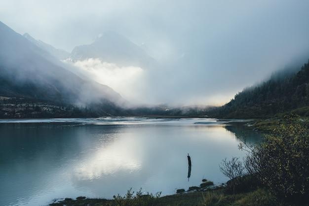 Klimatyczny krajobraz alpejski z górskim jeziorem i wysoką pokrytą śniegiem górą w gęstych niskich chmurach. piękna sceneria niskiego oświetlenia ze spiczastym szczytem w gęstej mgle i złotym odbiciem słońca w jeziorze.