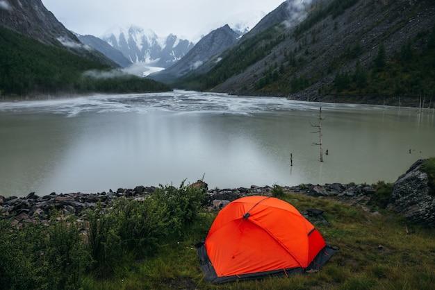 Klimatyczny krajobraz alpejski z pomarańczowym namiotem na brzegu zielonego górskiego jeziora i zaśnieżonych gór w deszczową pogodę. ponura sceneria z deszczowymi kręgami na wodzie górskiego jeziora i niskimi chmurami w dolinie