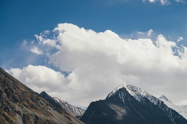 Klimatyczny krajobraz alpejski z sylwetką wysokiej góry ze śniegiem na szczycie pod błękitnym pochmurnym niebem. dramatyczna górska sceneria z pięknym ośnieżonym spiczastym szczytem i wysoką ośnieżoną ścianą górską