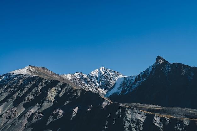 Klimatyczny krajobraz górski z ciemnymi sylwetkami gór. ostry skalisty szczyt i pokryty śniegiem szczyt w słońcu. alpejska sceneria z czarno-pomarańczową górą ze szczytem w słońcu jesienią.
