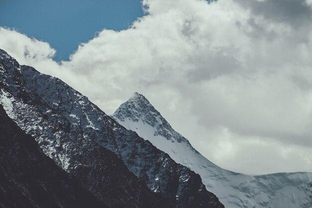 Klimatyczny krajobraz górski z wysokim ośnieżonym szczytem pod zachmurzonym niebem w wyblakłych odcieniach. ponura górska sceneria z wielką ośnieżoną sterczyną w chmurach w ciemnych kolorach. niesamowity śnieżny spiczasty szczyt.