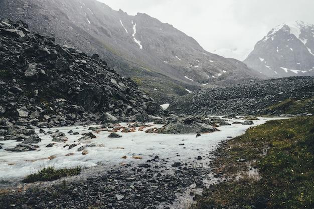 Klimatyczny krajobraz z górskim potoku wśród moren w deszczową pogodę. ponura sceneria z mleczną rzeką z zaśnieżonych gór. kamienie z mchem i porostami w strumieniu wody. górska rzeka wśród skał.