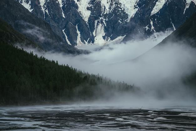 Klimatyczny krajobraz z wielką ośnieżoną górą i gęstymi niskimi chmurami wśród leśnych sylwetek w górskiej dolinie ze strumieniami wody z lodowca. grube, niskie chmury wśród sylwetek drzew na zboczu
