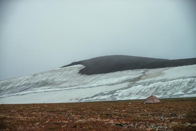 Klimatyczny minimalistyczny górski krajobraz z małym lodowcem na skalistym zboczu wzgórza wewnątrz niskiej chmury. zbocze góry z lodowcem w gęstej mgle. namiot w dolinie wysokogórskiej w niskiej chmurze. mglista góra.