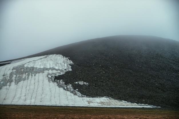 Klimatyczny minimalistyczny górski krajobraz z małym lodowcem na skalistym zboczu wzgórza wewnątrz niskiej chmury. zbocze góry z małym lodowcem w gęstej mgle. wysokogórska dolina w niskiej chmurze. słaba widoczność.