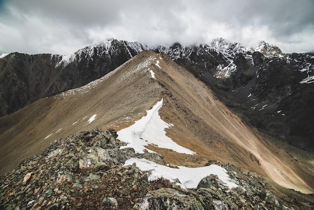 Klimatyczny, minimalistyczny krajobraz alpejski po masywne zaśnieżone pasmo górskie. śnieg lub śnieg na skalistym wzgórzu grzebieniowym. chmura niebo nad dużym śniegiem grzbietu. rock of boulder stream. majestatyczna sceneria na dużej wysokości