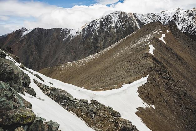 Klimatyczny, minimalistyczny krajobraz alpejski z masywnym ośnieżonym pasmem górskim i firnem na skalistym wzgórzu grzebieniowym. zachmurzone niebo nad dużym, pokrytym śniegiem grzbietem. rock of boulder stream. majestatyczna sceneria na dużej wysokości.