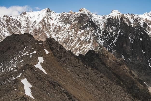 Klimatyczny, minimalistyczny krajobraz alpejski z masywnym zaśnieżonym pasmem górskim. śnieg lub firn na grzebieniowym skalistym wzgórzu. błękitne niebo nad ośnieżoną granią. rock of boulder stream. majestatyczna sceneria na dużej wysokości.