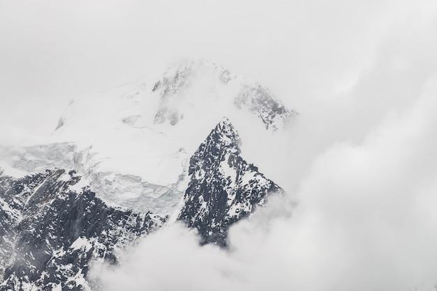 Klimatyczny, minimalistyczny krajobraz alpejski z ogromnym wiszącym lodowcem na zaśnieżonym szczycie góry