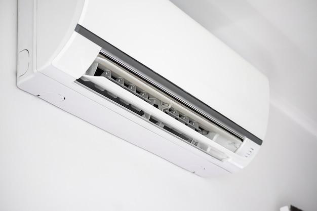 Klimatyzator na tle wnętrza pokoju białej ściany