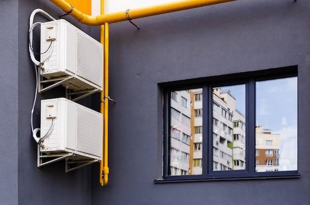 Klimatyzator z dwoma blokami (skrzynkowymi) z przodu budynku.