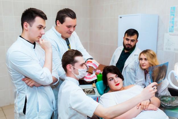 Klinika dentystyczna. grupa profesjonalnych lekarzy omawia leczenie stomatologiczne na zdjęciach rentgenowskich w gabinecie. nowoczesna edukacja medyczna.