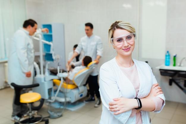 Klinika dentystyczna. portret profesjonalnego dentysty na tle pracującego zespołu lekarzy. pojęcie edukacji medycznej i ubezpieczenia medycznego.