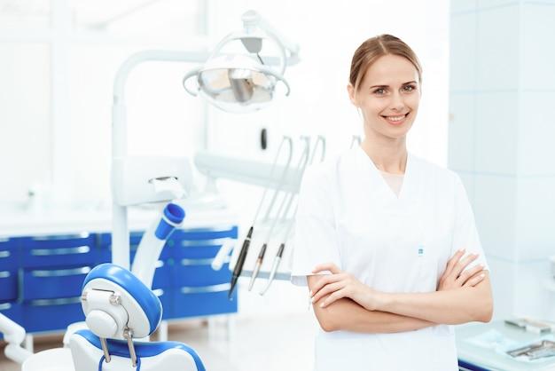 Klinika stomatologii. uśmiechnięta pielęgniarka pozuje przeciw.