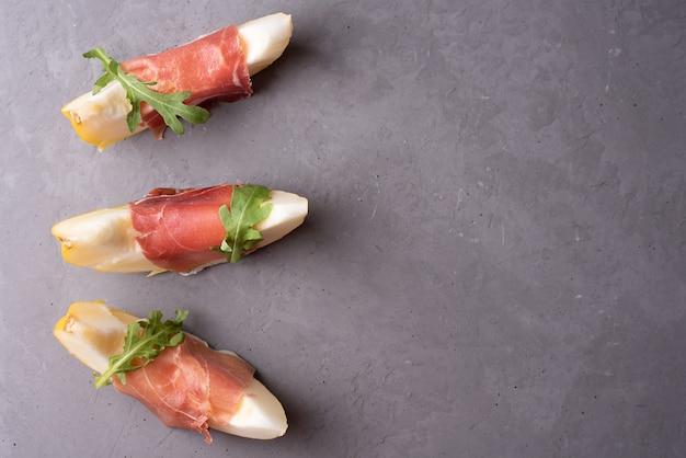 Kliny świeżego melona z prosciutto i rukolą na szarym tle betonu, włoska szynka i przystawka owocowa, miejsce.