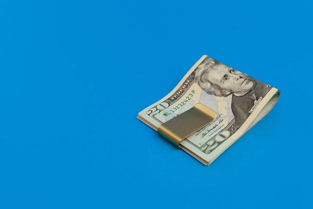 Klips do pieniędzy z banknotami dolarowymi na niebieskim tle