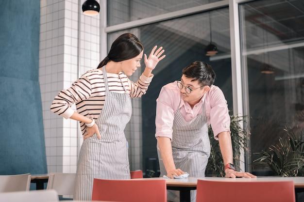 Kłócąc się o kolegę. ciemnowłosa emocjonalna kelnerka kłóci się z koleżanką w okularach