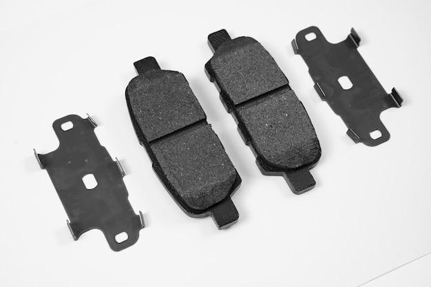 Klocek hamulcowy na białym tle. część układu hamulcowego, główny element roboczy. antyodrzutowy nacisk na dodatkowe mocowanie pojazdu podczas postoju. sklep z częściami samochodowymi. warsztat samochodowy