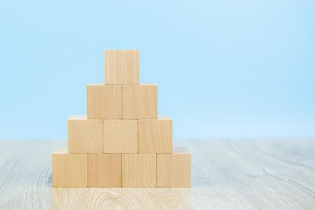 Klocki drewniane ułożone w kształcie piramidy bez grafiki.