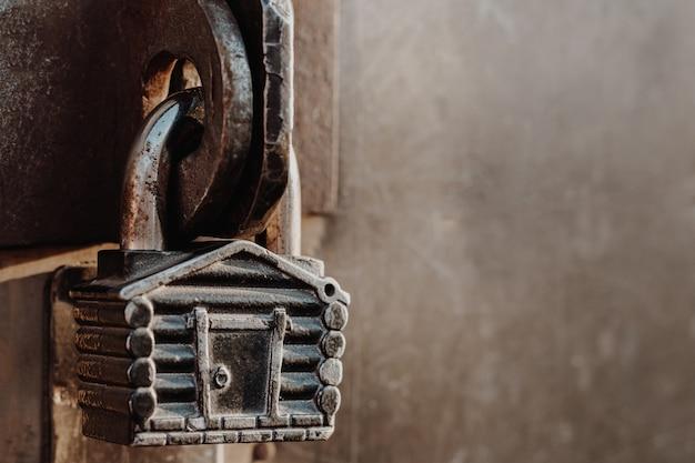 Kłódka w kształcie chaty wisi na zawiasach zamkniętej bramy. metalowe bramy.